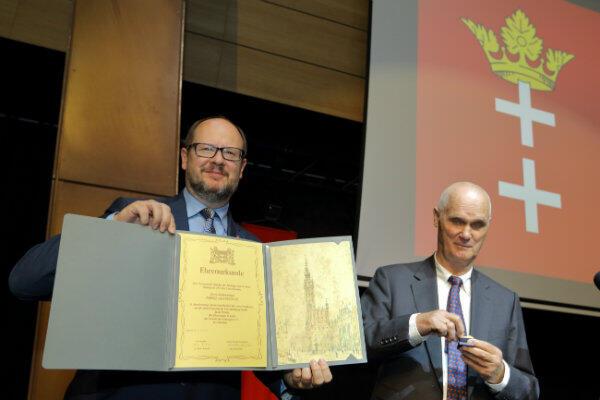 Dr Heiko Körnich (z prawej) zaraz wepnie Złotą Szpilkę w klapę marynarki prezydenta Gdańska Pawła Adamowicza.