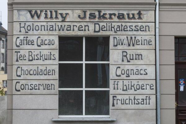 Napis głosi, że w tym miejscu znajdował się delikatesowy sklep spożywczy Willy'ego Iskrauta.