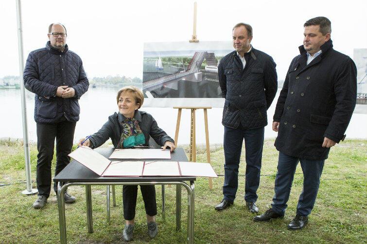List intencyjny podpisuje wójt Magdalena Kołodziejczak. Stoją od lewej: prezydent Adamowicz, marszałek Struk, wiceminister Orłowski. Za nimi - plansza z wizualizacją mostu, który ma być wybudowany.
