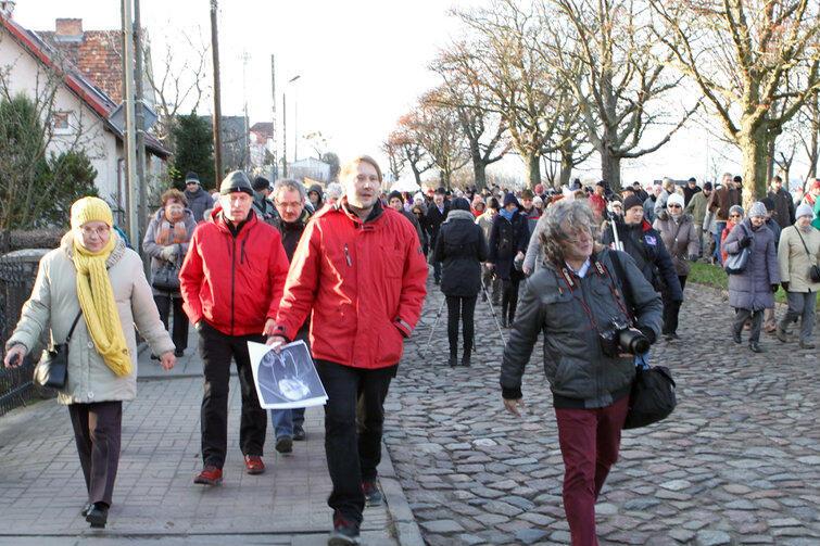 Tłum spacerowiczów idzie ul. Lubuską. Na pierwszym planie, w czerwonej kurtce - przewodnik Aleksander Masłowski.