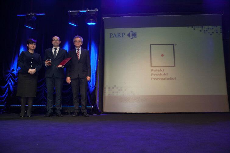Prezes AssisTech Bartosz Kunka (stoi w środku) odebrał nagrodę z rąk prezes PARP Bożeny Lublińskiej-Kasprzak, przewodniczącej kapituły konkursu. Na zdjęciu także prof. Wojciech Dominik, członek kapituły.