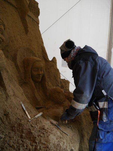 Z piasku wyłania się postać Marii z Dzieciątkiem.