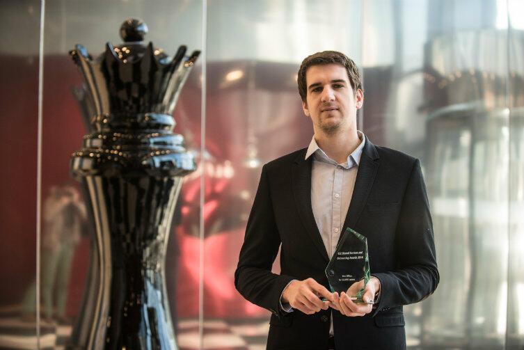 Paweł Pinker, z działu marketingu Olivia Business Centre, stoi dumnie z nagrodą dla biurowca.