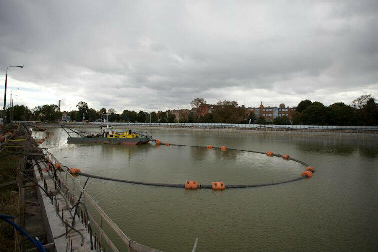 Wrzesień 2013 r. Prace budowlane trwają. Na basenie wypełnionym wodą pływa barka podająca cement.