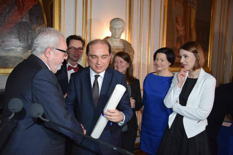 Pedro Agramunt wręcza pamiątkowy dyplom delegacji ECS. Cała sala w tym czasie na stojąco bije brawo.
