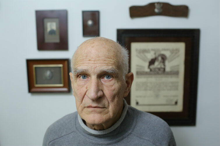 Andrzej Stachecki na tle ściany z pamiątkami po ojcu