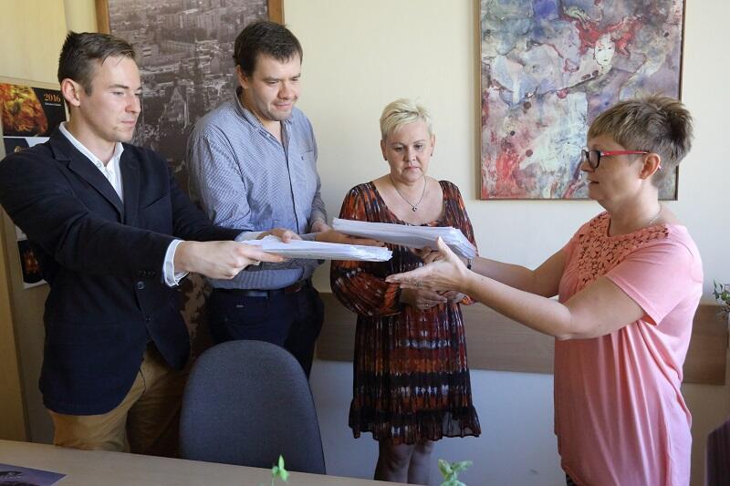 Od lewej: Juliusz Grabowski, Szymon Mazurkiewicz i Ewa Okuniewska składają teczkę z podpisami mieszkańców Suchanina