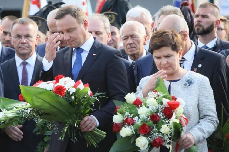 Prezydent RP Andrzej Duda i premier rządu RP Beata Szydło robią znak krzyża przed bramą nr 2. Czy PiS uzna Wałęsę za bohatera czy za agenta SB Bolka, jak mówi o nim wielu polityków tej partii?
