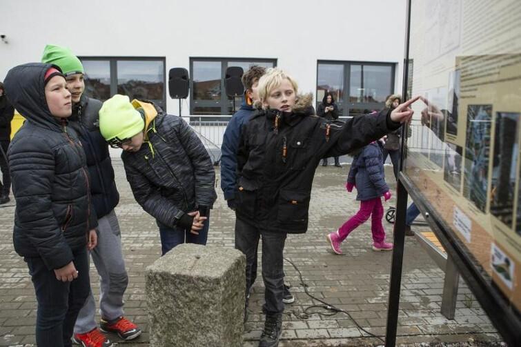 Historia i współczesność: dzieci ze szkoły w Kokoszach stoją wokół słupa granicznego z Wolnego Miasta Gdańska i czytają tablicę o historii naszego miasta.