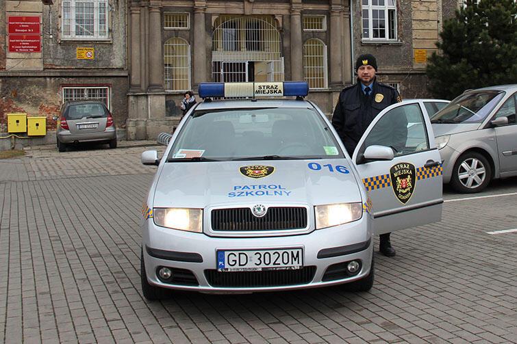 Artur Sokołowski i radiowóz Straży Miejskiej z napisem Patrol Szkolny
