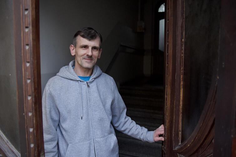 Piotr Poźniak w zabytkowych drzwiach kamienicy z 1907 roku