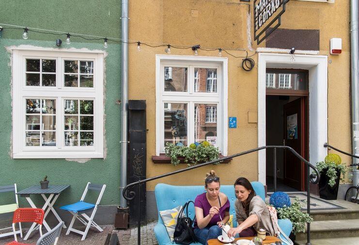Znak Free Toilet dyskretnie wystaje zza roślinek przed Matką i Córką. Sara Pisarewicz (gość kawiarni, po prawej): - Super pomysł! Toalety były dotąd słabo oznaczone, ciężko było je znaleźć