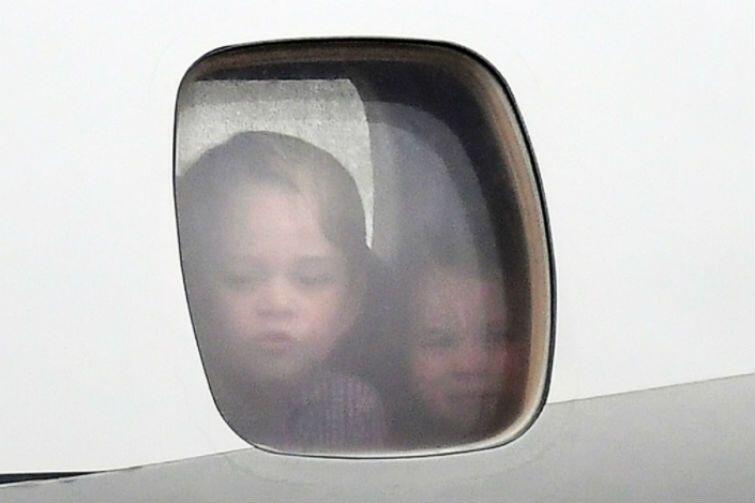 Warszawa, 17 lipca. Małe książątka - Charlotte i George - patrzą przez szybę samolotu na płytę lotniska