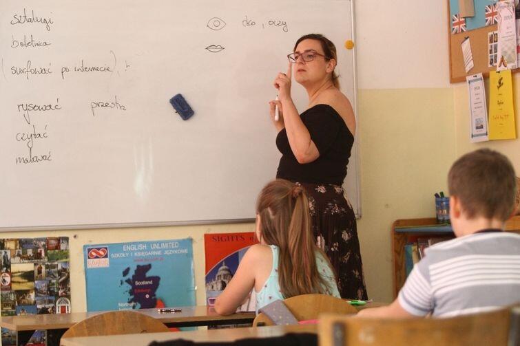 Joanna Wróbel przy tablicy w czasie lekcji dla dzieci z Ukrainy i Rosji. Tu grupa początkująca nauczy się za chwilę, jak opisać twarz: oczy, policzki, brwi, usta