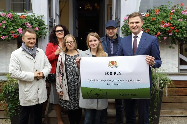 Wyróżnienie dla Kawiarni Perro Negro. Pośrodku stoi Agnieszka Dąbrowska (przedstwicielka Perro Negro), na lewo od niej - ogrodniczka miejska Joanna Paniec i blogerka Ewa Kowalska