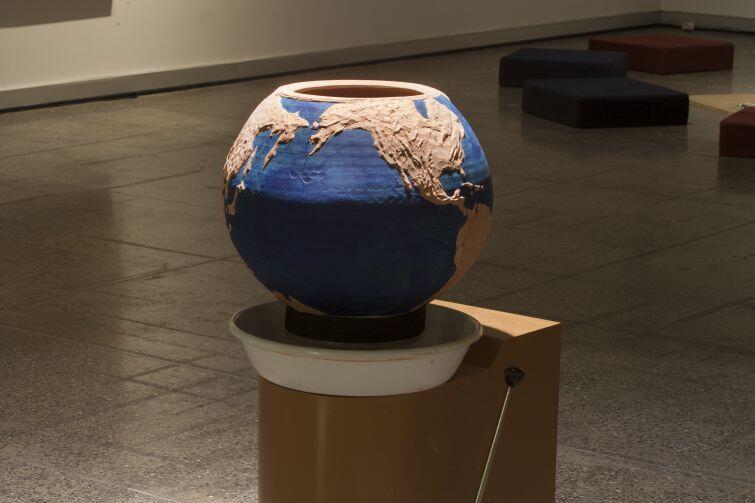 Ewoluująca praca Federico Guzmána - instalacja, której centralną częścią jest donica przypominająca kulę ziemską, w której artysta umieścił nasiona różnych roślin. Nad donicą umieszczona została lampa ogrzewająca, która umożliwi roślinom wzrost. Instalacja będzie ewoluować w miarę rozwoju roślin