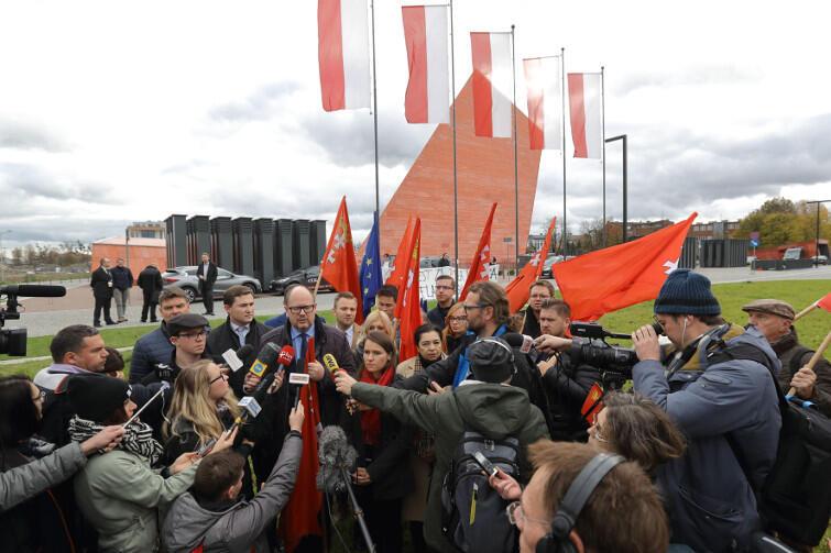 Paweł Adamowicz i Agnieszka Pomaska (PO) przed budynkiem MIIWŚ tłumaczą, dlaczego flagi Gdańska i UE powinny wrócić ich zdaniem na maszty