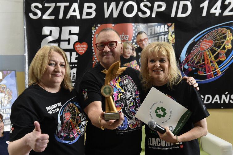 Wizyta Jurka Owsiaka w SP nr 8 w 2017 r. Gość otrzymał statuetkę Przyjaciela Szkoły z rąk dyrektor Marii Rudnickiej i Katarzyny Kędzioł