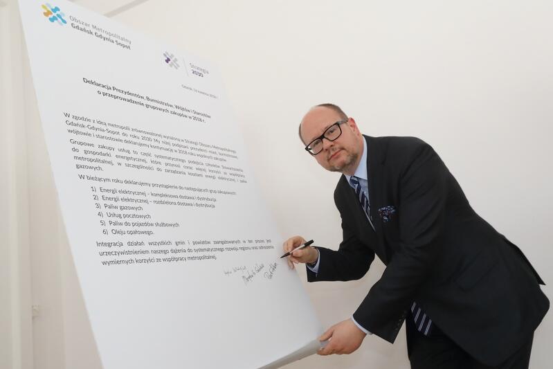 Paweł Adamowicz, prezydent Gdańska i przewodniczący zarządu Obszaru Metropolitalnego G-G-S składa podpis pod deklaracją
