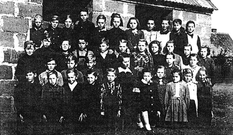 Pierwsi uczniowie nowo wybudowanej szkoły na tle budynku gospodarczego - 1948 r.