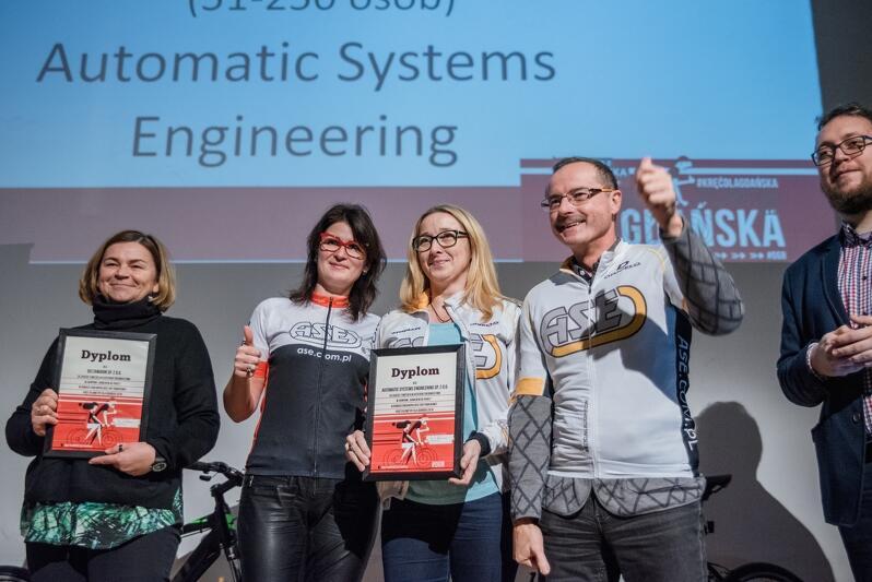 Radość laureatów II miejsca w najliczniejszej kategorii firm średnich - rowerzyści z Automatic Systems Engineering stanęli na podium w drużynowych koszulkach, obok - przedstawicielka firmy, która zdobyła III miejsce -Deltamarin
