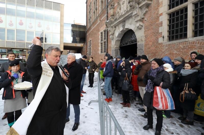 Wigilia dla potrzebujących w gdańskiej Zbrojowni, ks. Ireneusz Bradtke święci opłatek przed składaniem życzeń
