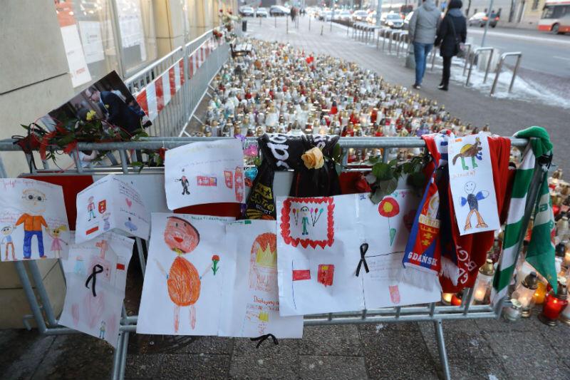 Znicze i rysunki dzieci przed wejściem do budynku Urzędu Miejskiego przy ul. Nowe Ogrody