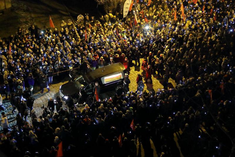 Karawan z trumną otoczony tłumem ludzi