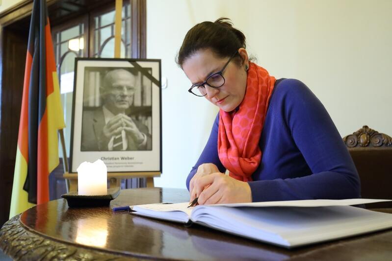 Aleksandra Dulkiewicz, pełniąca obowiązki prezydenta Gdańska, wpisuje się do księgi kondolencyjnej. Obok - portret Christiana Webera