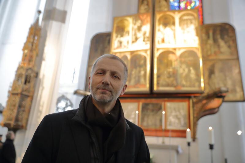 Krzysztof Owsiany, szef zespołu konserwatorów na tle ołtarza
