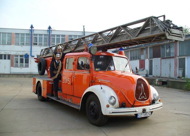 Strażacy ze Stoczni Gdańskiej w drodze na wodowanie, w tle jednostka zakładowej straży pożarnej na Wyspie Ostrów