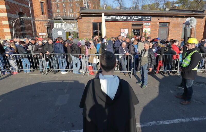 Z przodu - plecy o. Pawła Koniarka, duszpasterza `Górki` , w tle - tłum oczekujących na pomoc