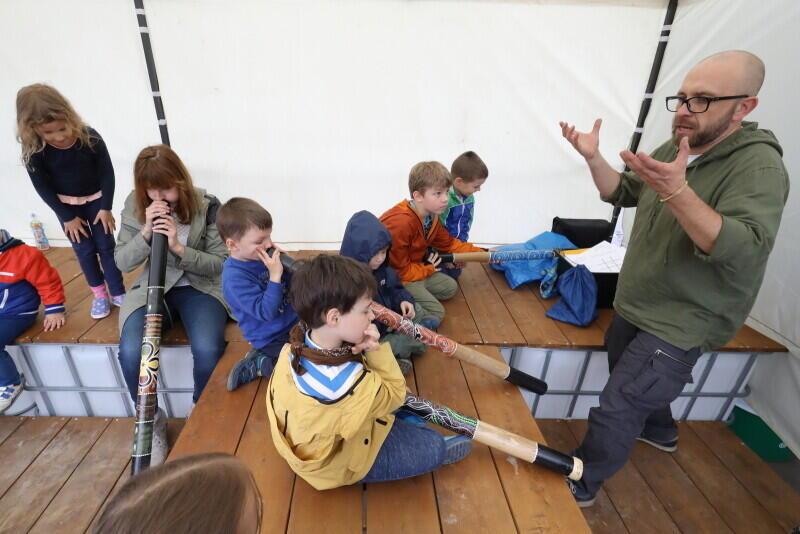 Robert Maciąg tłumaczy jak Aborygeni wydobywają dźwięki z didgeridoo - uczestnicy próbują to zrobić