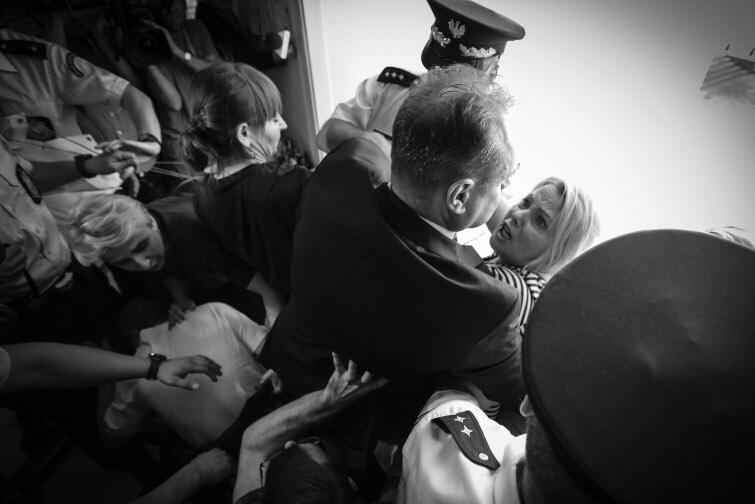 """Autor: Sławomir Kamiński, """"Gazeta Wyborcza"""". Warszawa, sejm. 37. dzień protestu rodziców i opiekunów osób niepełnosprawnych. Protestujący próbują rozwiesić transparent w języku angielskim na zewnętrznej ścianie budynku, by zwrócić uwagę zagranicznych mediów przed zbliżającym się Zgromadzeniem Parlamentarnym NATO w Warszawie, lecz straż marszałkowska im to uniemożliwia. Na zdjęciu matka niepełnosprawnego Jakuba Iwona Hartwich w starciu ze strażnikiem. 24 maja 2018"""