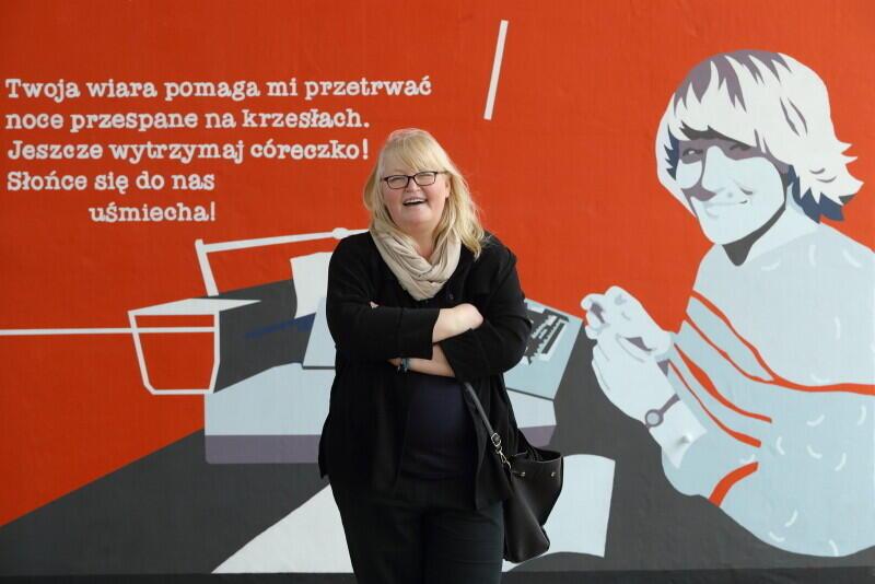 """Ewa Korczyńska na tle malowidła przedstawiającego jej matkę Jadwigę """"Jagodę"""" Piątkowską"""