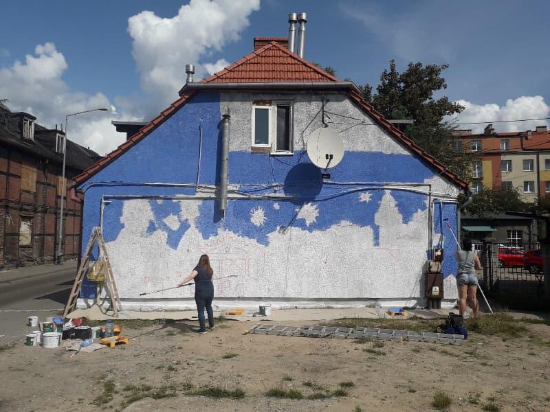 W pracy nad muralem pomagają dzieciom dorośli. W środę, 14 sierpnia 2019 r. przygotowywali ścianę pod obraz