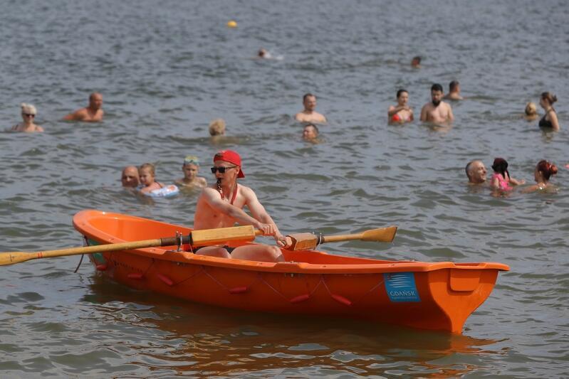 Jeden z gdańskich ratowników podczas pracy na kąpielisku Stogi. Monitoruje sytuację z łódki, od strony wody. W tym samy czasie dwoje innych robi to samo, od strony plaży. Na każde sto metrów linii brzegowej przypada troje ratowników
