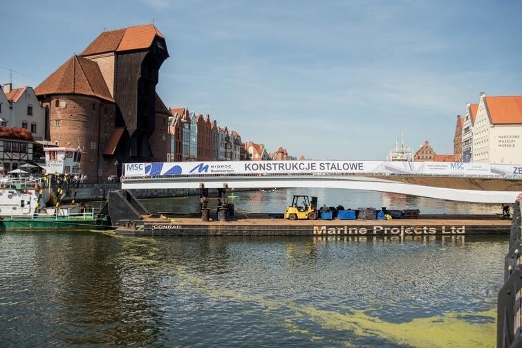 Obrotowa część kładki dopłynęła do śródmieścia Gdańska w piątek około godz. 14. Po przeprowadzeniu wszystkich pomiarów, będzie ona zsuwana z pontonu, na którym była transportowana, bezpośrednio na wybudowany fundament