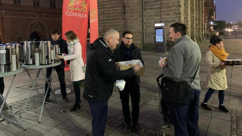 Zastępca prezydent Gdańska Piotr Kowalczuk częstuje drożdżówkami przy budynku LOT