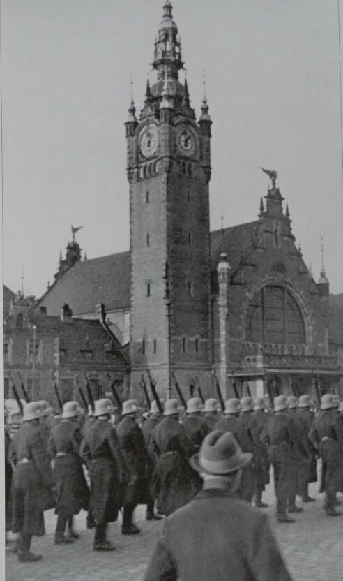 Niemcy zajmują Gdańsk. Oddziały Rzeszy wkraczają do miasta. Żołnierze jednej z nazistowskich formacji militarnych paradują przed Dworcem Głównym