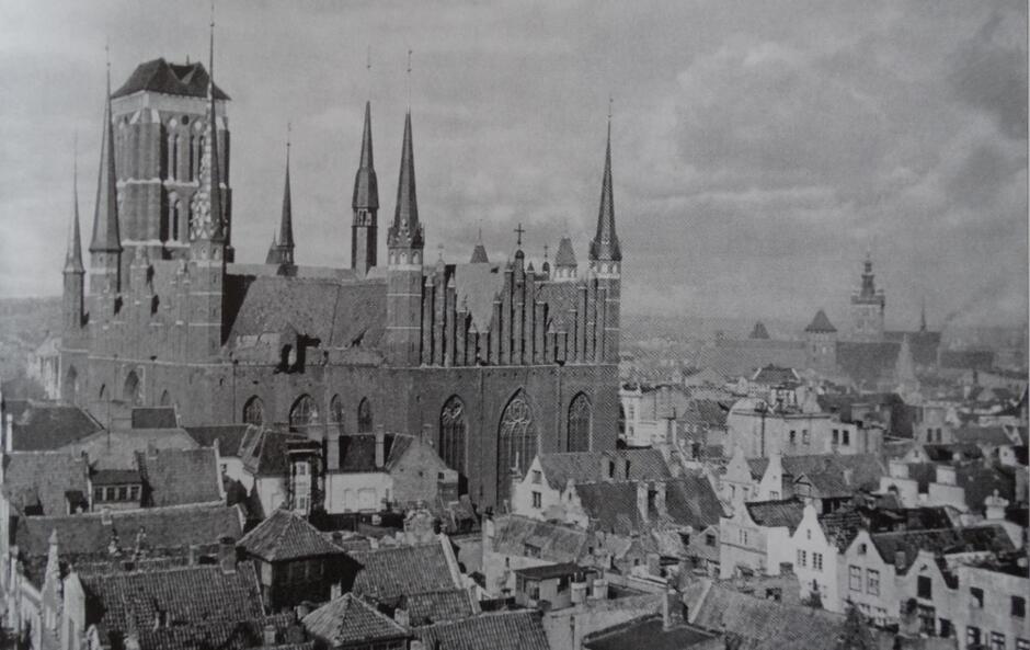 Wysokie, ciasno zabudowane kamieniczkami gdańskie uliczki. Nad nimi wznosi się majestatyczna bryła kościoła Panny Marii