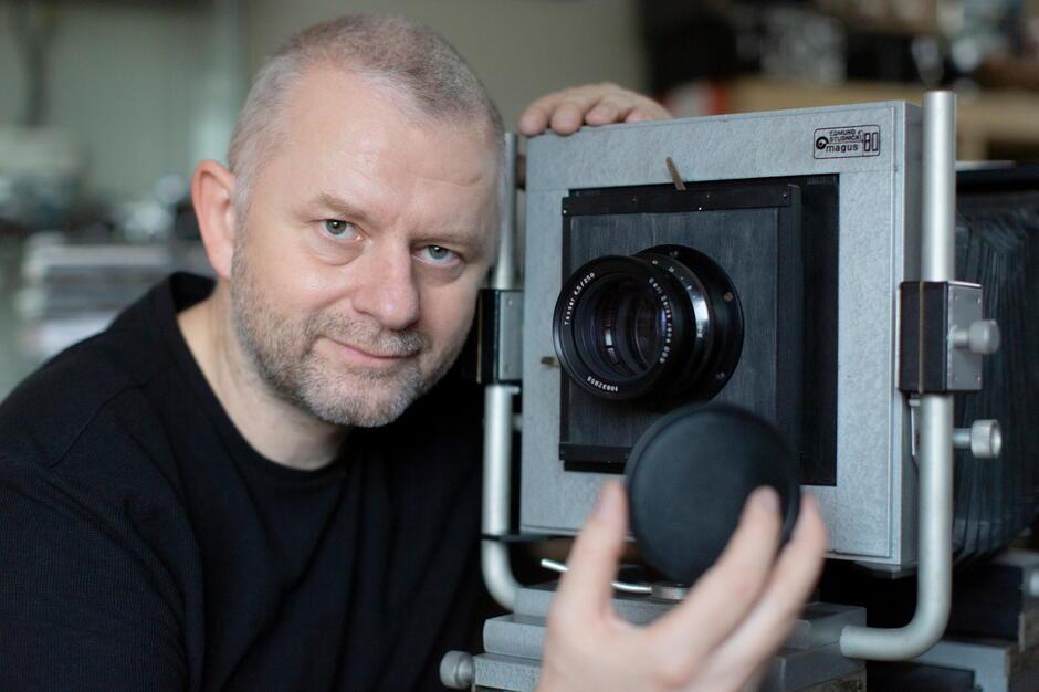 Grzegorz Mehring - fotoreporter i pasjonat starych polskich aparatów fotograficznych. Pozuje ze swoim Magusem 80, aparatem studyjnym z manufaktury Edmunda Studnickiego