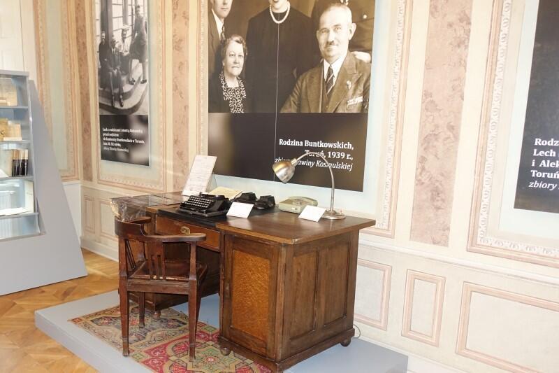 Biurko Lecha Bądkowskiego i maszyna do pisania, do obejrzenia na wystawie w Muzeum Piśmiennictwa i Muzyki Kaszubsko-Pomorskiej w Wejherowie. Na ścianie - zdjęcie rodzinne, wykonane w latach 30. XX w.