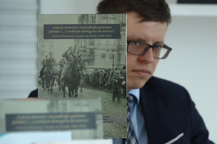 Krzysztof Drażba, naczelnik Oddziałowego Biura Edukacji Narodowej IPN w Gdańsku, prezentuje wydawnictwo o okolicznościach, w jakich Kujawy i Pomorze wróciły do Polski w latach 1918-1920