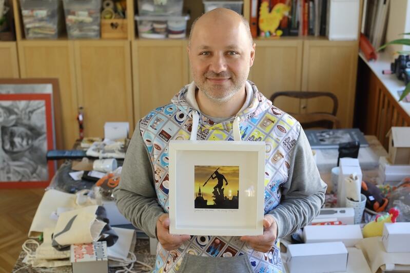 Krzysztof Skrzypski, prezes Ciekawej Spółdzielni Socjalnej, która prowadzi kawiarnię cieKAWA przy ul. Świętojańskiej, prezentuje fotografię autorstwa Macieja Kosyczarza licytowaną na fejsbukowym Bazarku na rzecz Spółdzielni, za nim - góra fantów na kolejne licytacje