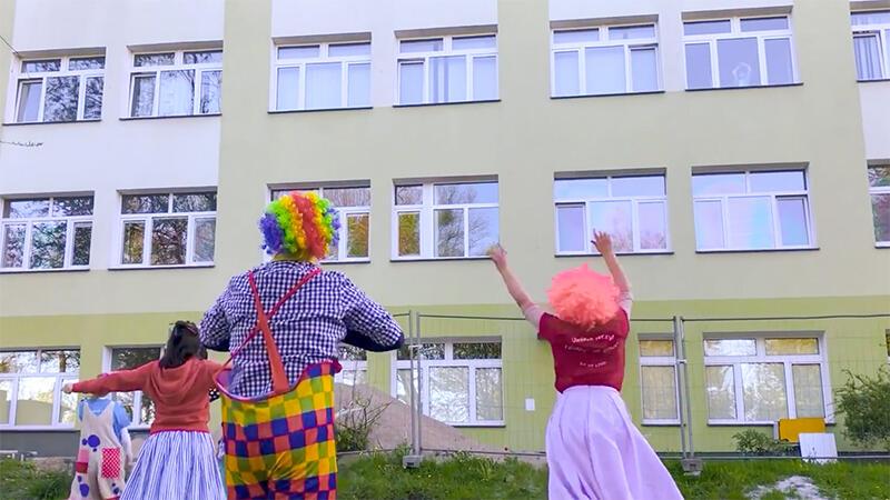 Wolontariusze Fundacji `Dr Clown` w tańcu pod oknami Szpitala Dziecięcego Polanki w Gdańsku