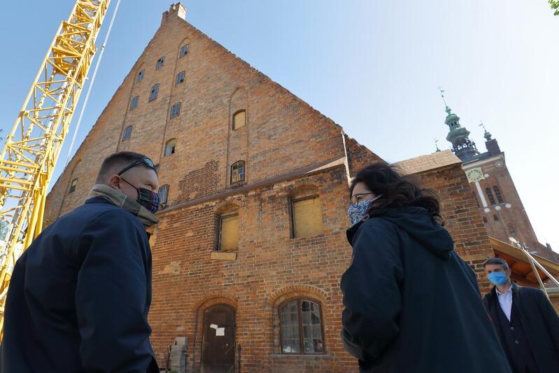 Widok ściany szczytowej Wielkiego Młyna od strony ul. Rajskiej. Do budynku wchodzą prezydent Aleksandra Dulkiewicz i Waldemar Ossowski, dyrektor Muzeum Gdańska