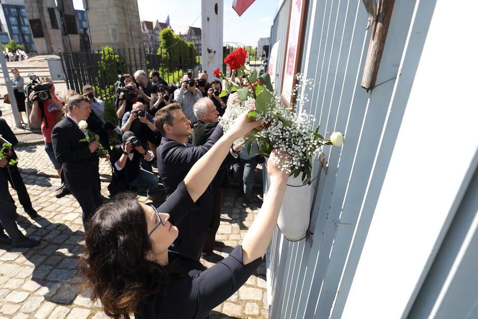 Przy historycznej Bramie nr 2 wetknięto białe i czerwone róże