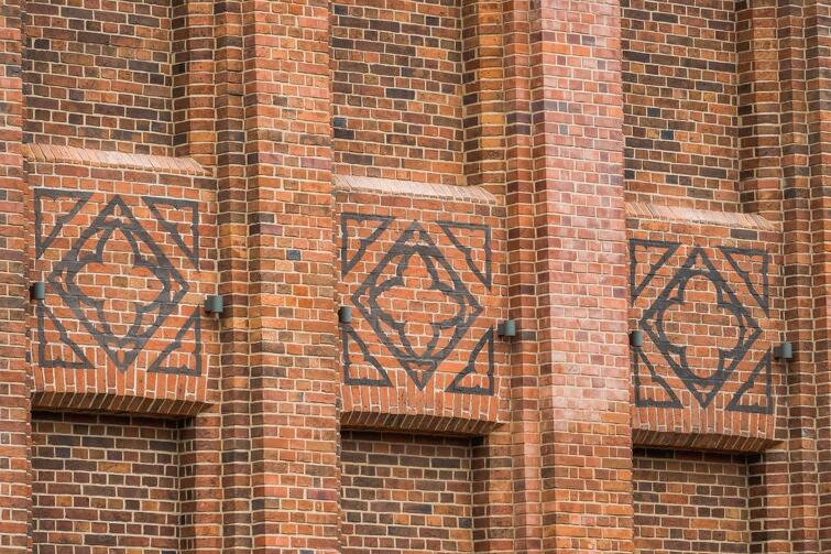 Tylko na północnej elewacji dawnej szkoły zachowały się malowidła wykonane farbą na cegle, które uzupełniono w brakujących miejscach
