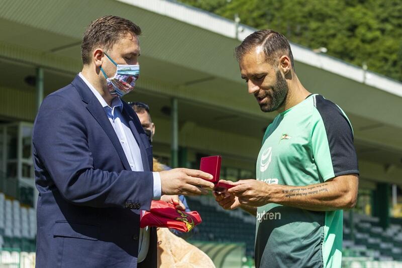 Na ręce kapitana Lechii Gdańsk - Flávio Paixão Piotr Borawski wręcza szczęśliwą monetę z wizerunkiem bursztynowego stadionu